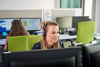 Frau am Arbeitsplatz mit Headset